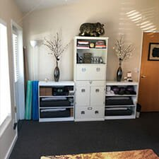 Interior space of Yoga Mojo & Movement Therapy studio in Vancouver, Washington showing all of the props (blankets, bolsters, blocks, tune-up balls, cards, etc.) that can be used in a yoga class