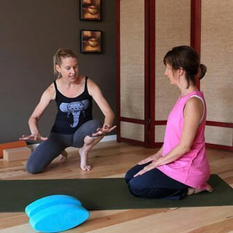 Jocellyn learns yoga hand placement for downward dog in a beginning yoga class in Vancouver, Washington at Yoga Mojo and Movement Therapy